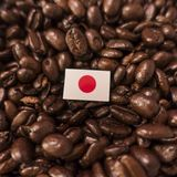 A Japan flag placed over roasted coffee beans stock photography