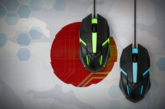 Japan flag and two mice with backlight. Online cooperative games. Cyber sport team. Japan flag and two modern computer mice with backlight. The concept of online stock images