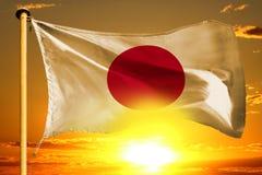 Japan flagga som väver på den härliga orange solnedgången med molnbakgrund Royaltyfri Foto