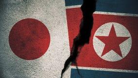 Japan gegen Nordkorea-Flaggen auf gebrochener Wand Stockbild