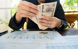 Japan-Geld in der Hand mit Aussagenpapier im Finanzkonzept Lizenzfreie Stockfotografie