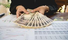 Japan-Geld in der Hand mit Aussagenpapier im Finanzkonzept Stockfotos