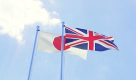 Japan and Great Britain, flags waving against blue sky. Two flags waving against blue sky. 3d image Stock Photography