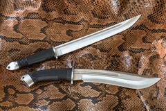 Knives for hunting, defense and assault on python snake skin. Very sharp blades for hunt and defense. The Japan hunting knives have very sharp blades, useful Royalty Free Stock Images