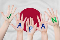 Japan inscription on the children`s hands against the background of a waving flag of the Japan.  royalty free stock photo
