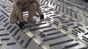 JAPAN, JANUARY 2016, US Soldier Turn Rail With Rolls In Aircraft. A US soldier turn a rail with rolls on it at a C17 cargo aircraft stock video footage