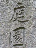 Japan/kinesiska bokstäver betyda trädgårds- ` för ` som inristas på stenväggen royaltyfri foto