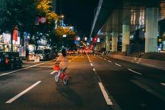 Japan kvinna som cyklar vägen på natten arkivbild