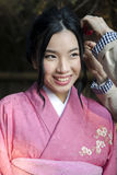 Young japanese girl in pink kimono. JAPAN, KYOTO, APRIL, 06, 2017 - Young japanese girl in national clothes doing a hairstyle for the evening performance in Gion Royalty Free Stock Photography