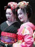 Beautiful Young and Mature Geisha walking in Kyoto old town Geisha district Japan. stock photos