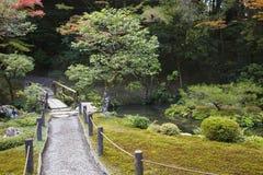 Japan Kyoto Tenju-an tempelträdgård med vandringsledet och bron Arkivfoto