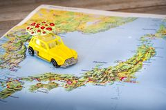 Japan map paper yellow beetle toy car background. Honshu, Japan, 7 April 2018 - Japan map with a yellow beetle toy car with umbrella on top royalty free stock image