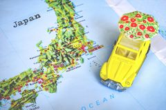 Japan map with a yellow beetle toy car with a white umbrella. Tokyo, Japan, 4 April 2018 - Japan map with a yellow beetle toy car with a white umbrella on it royalty free stock images