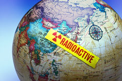 Japan Fukushima Radioactive Crisis. A world globe with a piece of radioactive tape stuck over Fukushima Japan Royalty Free Stock Photo