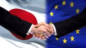 Japan och för europeisk union handskakning, internationellt kamratskap, flaggabakgrund royaltyfri bild