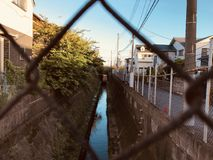 A small river located between houses in Japan. stock photography