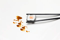 Sushi Hosomaki in The Chopsticks. Typical Japanese Food. Japan sushi roll in the chopsticks isolated on white background and decorated with soy sauce Royalty Free Stock Photography