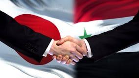 Japan and Syria handshake, international friendship relations, flag background. Stock photo stock photography
