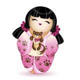Japan tafsar den nationella kokeshidockan in i en rosa kimono med en modell av den bruna katten I hennes händer rymmer hon en lit Royaltyfria Bilder