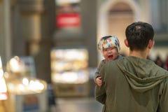 Japan, Tokyo, 04/08/2017 Ein schreiendes asiatisches Kind in den Armen des Vatis lizenzfreie stockfotografie