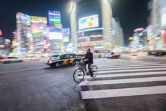 A man rides a bicycle passing the busy street of Shibuya crossing royalty free stock images