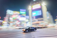 A taxi zooms pass the busy street of Shibuya crossing, Japan stock photos