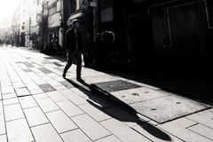 Man with long shadow walks along the street of Japan stock photos