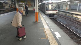 Old woman waits for a train to arrive in Tokyo, Japan royalty free stock image