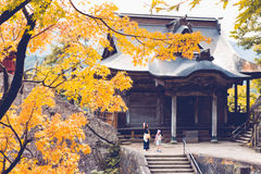 Japan. Travelers visit to the shrine of Yamadera, a famous Buddhist Temple perched on top of a rocky cliff in Yamagata Japan, with maple tree on the foreground royalty free stock photo
