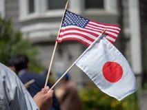 Japan- und USA-Handflaggen, die vom Kind wellenartig bewegt werden lizenzfreie stockfotografie