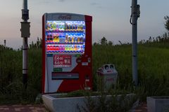 Japan Vending Machine in a remote and grassy area with can and bottle bin stock images