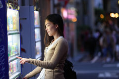 Japan vending machines - Tokyo woman buying drinks stock image