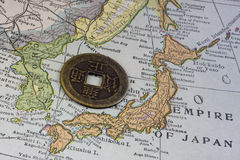 Japan on vintage map and old coin. Empire of Japan on a vintage map (1926) and old Japanese coin with square hole