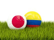 Japan vs Colombia. Soccer concept. Footballs with flags on green Royalty Free Stock Photos