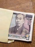 Japan 10000 yen räkning i kuvertet Arkivfoto