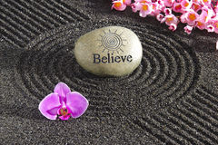 Japan zen garden. With stone of believe and orchid flower Royalty Free Stock Photo