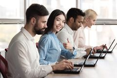 Japaneese girl accompanied with co-workers and shows thumb up. Female programmer accompanied with her team showing approval gesture, thumb up Royalty Free Stock Image