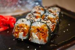 Japaner rollt mit Aal auf Schwarzblech Lizenzfreie Stockbilder