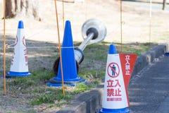 Japaner tragen nicht Zeichen vor eingestürztem Straßenlaterne ein Lizenzfreies Stockfoto