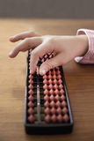 Japanese Abacus. Close up of a child´s hand  on the beads of a Japanese abacus (Soroban). An Abacus or counting frame is an instrument used for performing Stock Photography