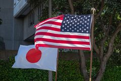 Japanese and American flags flowing in the wind stock images