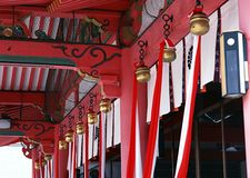 Japanese architectural decorative items with bells and red cloth royalty free stock image
