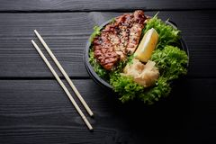 Japanese or asian cuisine. Salad with grilled meat or fish with lettuche, lemon and ginger stock photography