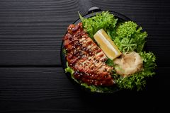 Japanese or asian cuisine. Salad with grilled meat or fish with lettuche, lemon and ginger stock image