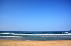 Japanese Autumn Beach. A white cloud is floating in the blue sky and white wave splash. This beautiful sandy beach in Japan, Kyushu, Fukuoka prefecture is royalty free stock photography