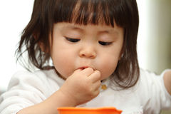 Japanese baby girl eating cereal Royalty Free Stock Photo