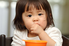 Japanese baby girl eating cereal Royalty Free Stock Image
