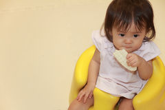 Japanese baby girl eating rice cracker Royalty Free Stock Photo
