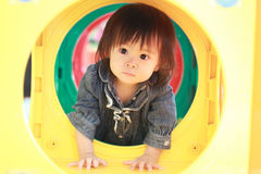 Japanese baby girl passing through a tunnel Stock Photography