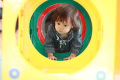 Japanese baby girl passing through a tunnel Royalty Free Stock Photography